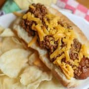 hot dog on a plate topped with chili with potato chips on the side