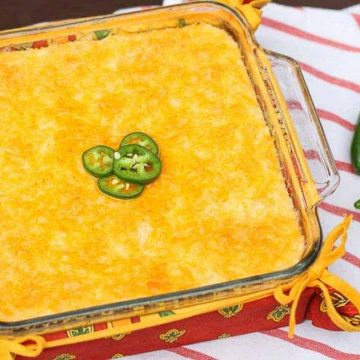 cheese grits in a glass square baking dish with two jalapenoes to the side