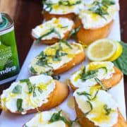 This lemon ricotta bruschetta is made with a creamy citrus ricotta blend topped with olive oil, sweet honey, fresh basil, and crunchy salt. The sweet, salty, and savory flavors combined with the crunchy and smooth textures makes this delicious gourmet appetizer. #lemon #bruschetta #ricotta