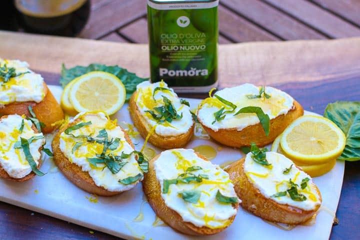 lemon ricottat brushetta on platter with can of  pomora olive standing to the back of the platter oil