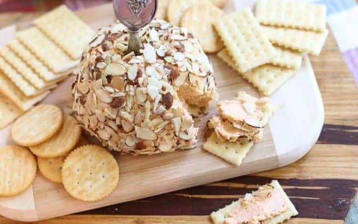 Port wine cheese ball on wood cutting board with crackers