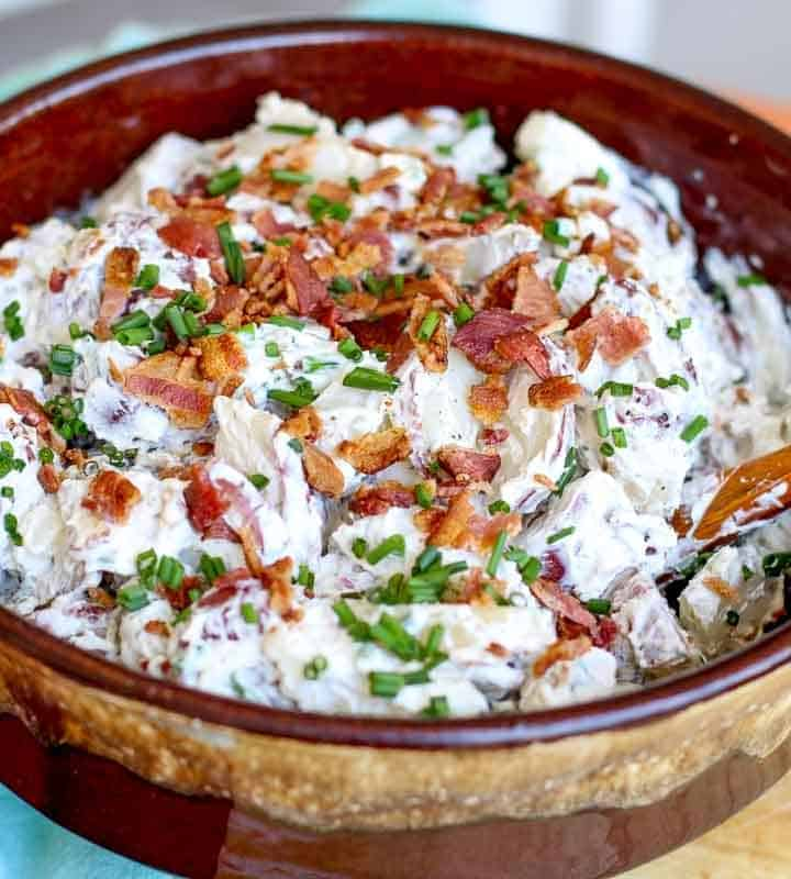 ranch potato salad in brown bowl with wooden spoon to the side
