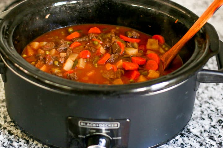 vegetable soup cooking in a slow cooker with wooden spoon set on the side