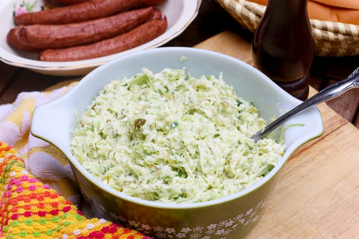 coleslaw in a bowl with a spoon to the side and hot dogs in the background