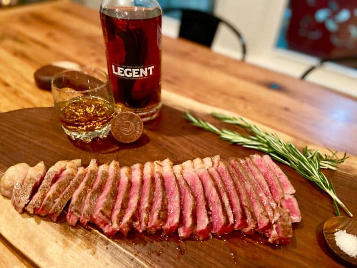 Legent Bourbon bottle with a glass of boubon to the side and sliced Wagyu steak on a wood chopping board